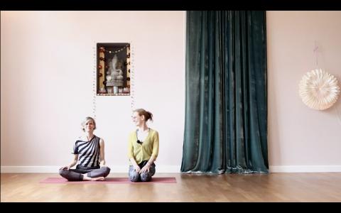 2 Frauen nebeneinander auf 2 Yogamatten. Sie lächeln sich an.
